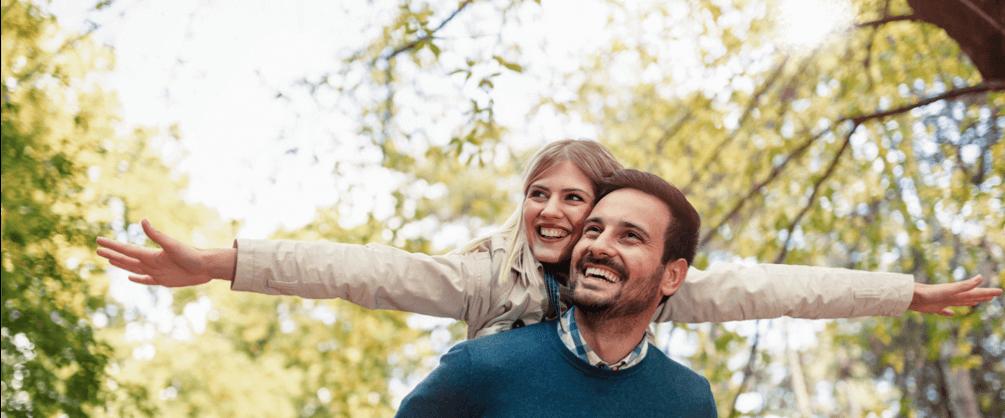 un homme porte une femme sur son dos, ils sourient. Des arbres en fond