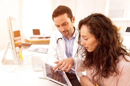 Une femme avec un médecin, le medecin lui montre quelque chose sur une tablette