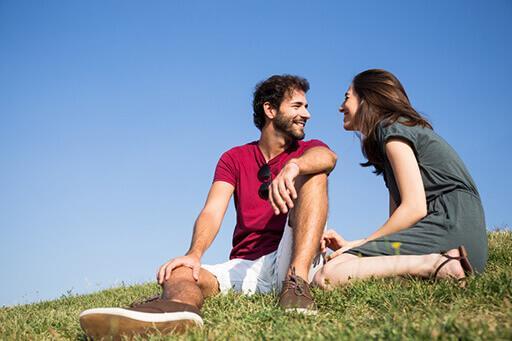 Ciel bleu en fond. Une femme et un homme se sourient, ils sont assis sur de l'herbe
