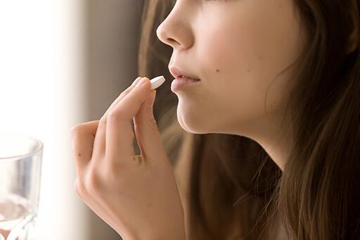 Un visage de femme, elle tient un verre d'eau dans un main et un médicament dans l'autre