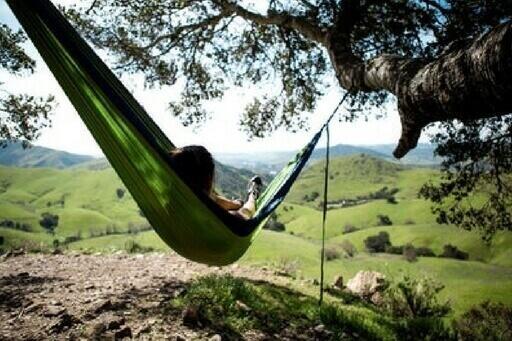 Une personne se repose dans un hamac vert et regarde les montagnes