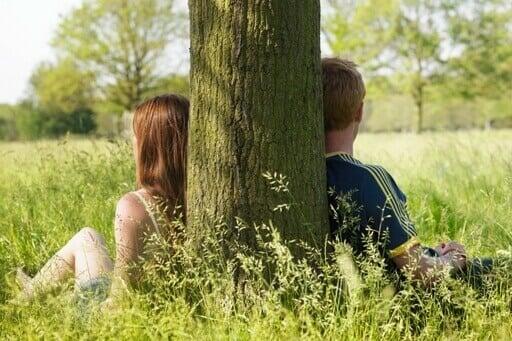 Un couple s'appuie sur un arbre. Ils regardent dans une position opposé