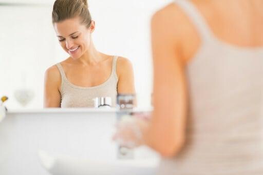 Une femme face à un miroir. Elle doit être dans sa salle de bain